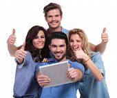 casual group of people reading good news on their tablet pad computer and make the ok thumbs up sign on white background