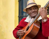 HAVANA,CUBA - JANUARY 15, 2014:Old afrocuban street musician playing the guitar next to a colonial h