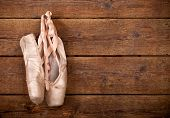picture of ballet shoes  - Old used pink ballet shoes hanging on wooden background - JPG