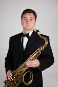 Saxophonist with a saxophone on a gray background.