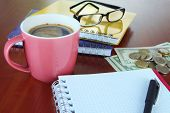 Office supplies with money and cup of coffee on wooden background