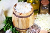 Composition with fresh and marinated cabbage (sauerkraut) in wooden barrel, on wooden table background