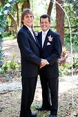 Handsome gay male wedding couple standing under a beautiful floral archway.
