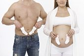 Young couple holding socks front of belly, woman pregnant, man half nude.