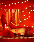 Photo of beautiful red romantic still life, two glass of champagne, shoe on high heels, luxury white
