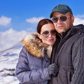 Closeup portrait of happy young family having fun in wintertime mountains, wearing fashionable sunglasses, travel and tourism concept
