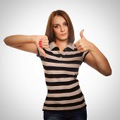 girl woman shows signs of yes and no, hand fingers isolated gray