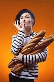 stock photo of french beret  - woman holding baguettes and shows that taste is delicious - JPG
