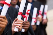stock photo of graduation gown  - group of multiracial graduates holding diploma - JPG