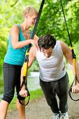 Young fitness man exercising with suspension trainer sling and personal sport trainer in City Park u