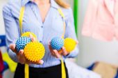 Female cleaner in laundry shop or textile dry-cleaning with drying or washing balls