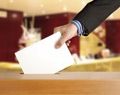 stock photo of voting  - Hand putting a voting ballot in a slot of box - JPG
