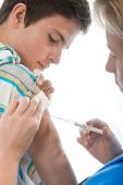 stock photo of flu shot  - male teenager getting a swine flu injection - JPG