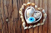 Shape Of Heart With Sea Shell And Amulet On A Wooden Table Backround