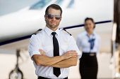 Portrait of confident pilot with arms crossed standing against stewardess and private jet at terminal