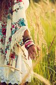 woman wearing boho style clothes touching grass, hand with lot of braceletes, summer day in the fiel