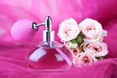 Perfume bottle with roses on pink fabric background