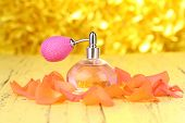 Perfume bottle with petals on yellow background