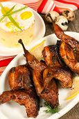 stock photo of quail  - Roasted quail in tomato sauce on the background of a garnish of mashed potatoes and quail eggs - JPG