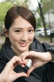 Asian young woman give you a gesture heart shape, close up portrait.