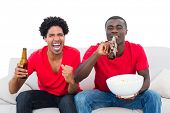 Football fans in red cheering on the sofa with beers and popcorn on white background
