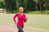 fitness, sport, training and lifestyle concept - smiling african american woman running on track out