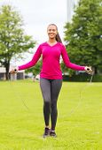 fitness, sport, training, park and lifestyle concept - smiling african american woman exercising wit