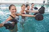 Smiling female fitness class doing aqua aerobics with foam dumbbells in swimming pool at the leisure
