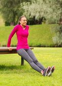 fitness, sport, training, park and lifestyle concept - smiling african american woman doing push-ups