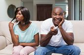 Bored woman sitting next to her boyfriend watching tv at home in the living room