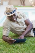 Smiling man relaxing in his garden using tablet pc on a sunny day