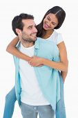 Happy casual man giving pretty girlfriend piggy back on white background