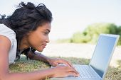 Casual pretty woman lying on the grass using her laptop on a sunny day in the countryside
