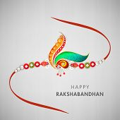 Beautiful rakhi decorated with peacock feathers and colorful pearls on grey background for Raksha Ba