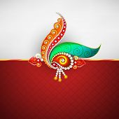 Beautiful peacock feathers and pearls decorated rakhi on grey and red background for Raksha Bandhan
