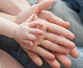 Father And Mother Holding Child's Hand