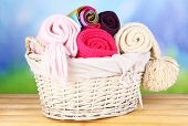 Warm knitted scarves in basket on wooden table on natural background