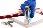 Fastening wooden frame using construction stapler isolated on white