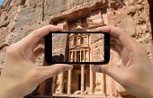 foto of petra jordan  - Hand holding mobile smart phone with blank screen Petra in Jordan - JPG