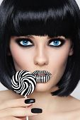 Conceptual portrait of young beautiful blue-eyed brunette with striped lips and fancy lollipop in he