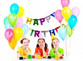 Three little girls having fun at the birthday party - isolated on a white.
