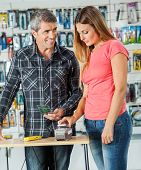 Couple paying for tools through smartphone in hardware store