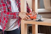 Midsection of female carpenter using sander on wooden shelf in workshop