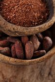 cocoa beans and grated dark chocolate in old texured spoons bowls on wood