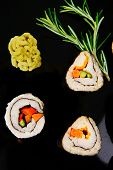 Roll with Cucumber , Cream Cheese with raw Tuna and Salmon inside. on black wooden plate. Japanese t