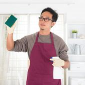 Asian guy housekeeping. House husband doing house chores, with home interiors. Male model.