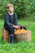 Boy sitting with basket full of chanterelles