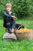Lad sitting near basket full of chanterelles