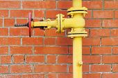 Yellow Metal Gas Pipeline With Valve On Background Of Red Brick Wall