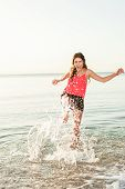 Happy woman making splashes on the beach at sunrise